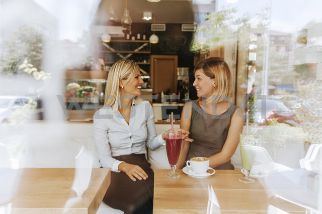 Two happy young women in a cafe - ZEDF00859