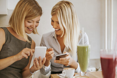 Two happy young women with smartphones in a cafe - ZEDF00862
