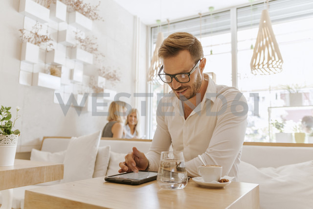 Man using tablet in a cafe with two women in background - ZEDF00865