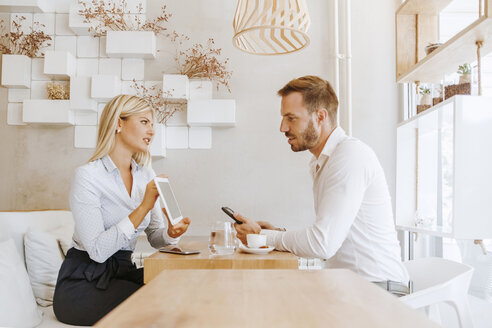 Businessman and businesswoman having a meeting in a cafe - ZEDF00871