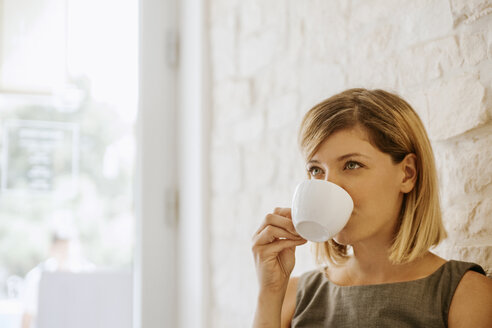 Young woman drinking cup of coffee - ZEDF00874