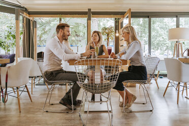 Three friends meeting in a cafe - ZEDF00886