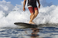 Indonesia, Bali, legs of surfer on a wave - KNTF00899