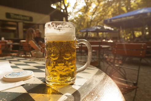 Beer mug on table in beer garden at evening twilight - FC01281