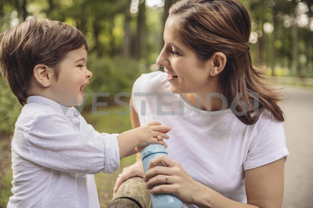 Mother and her little son having fun together in a park - MFF03972