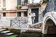 Italy, Venice, bridal couple standing  face to face at canal - DIGF02850
