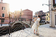 Italy, Venice, dancing bridal couple at sunrise - DIGF02862