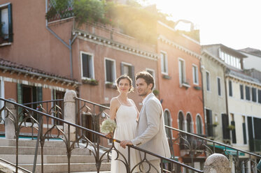Italy, Venice, bridal couple standing on stairs at sunrise - DIGF02865
