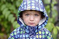 Portrait of little boy with dirty face wearing hooded jacket in rain - LBF01641