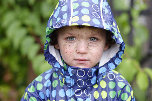 Portrait of little boy with dirty face wearing hooded jacket in rain - LBF01641