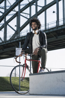 Man on bicycle in front of bridge - SBOF00668