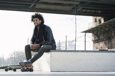 Smiling man with longboard sitting in skatepark under bridge holding a smartphone - SBOF00671