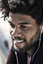 Portrait of smiling man listening to music on his earphones - SBOF00674