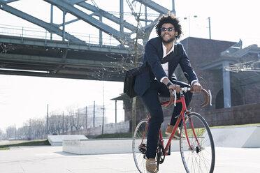 Smiling businessman riding bicycle at riverside bridge - SBOF00677