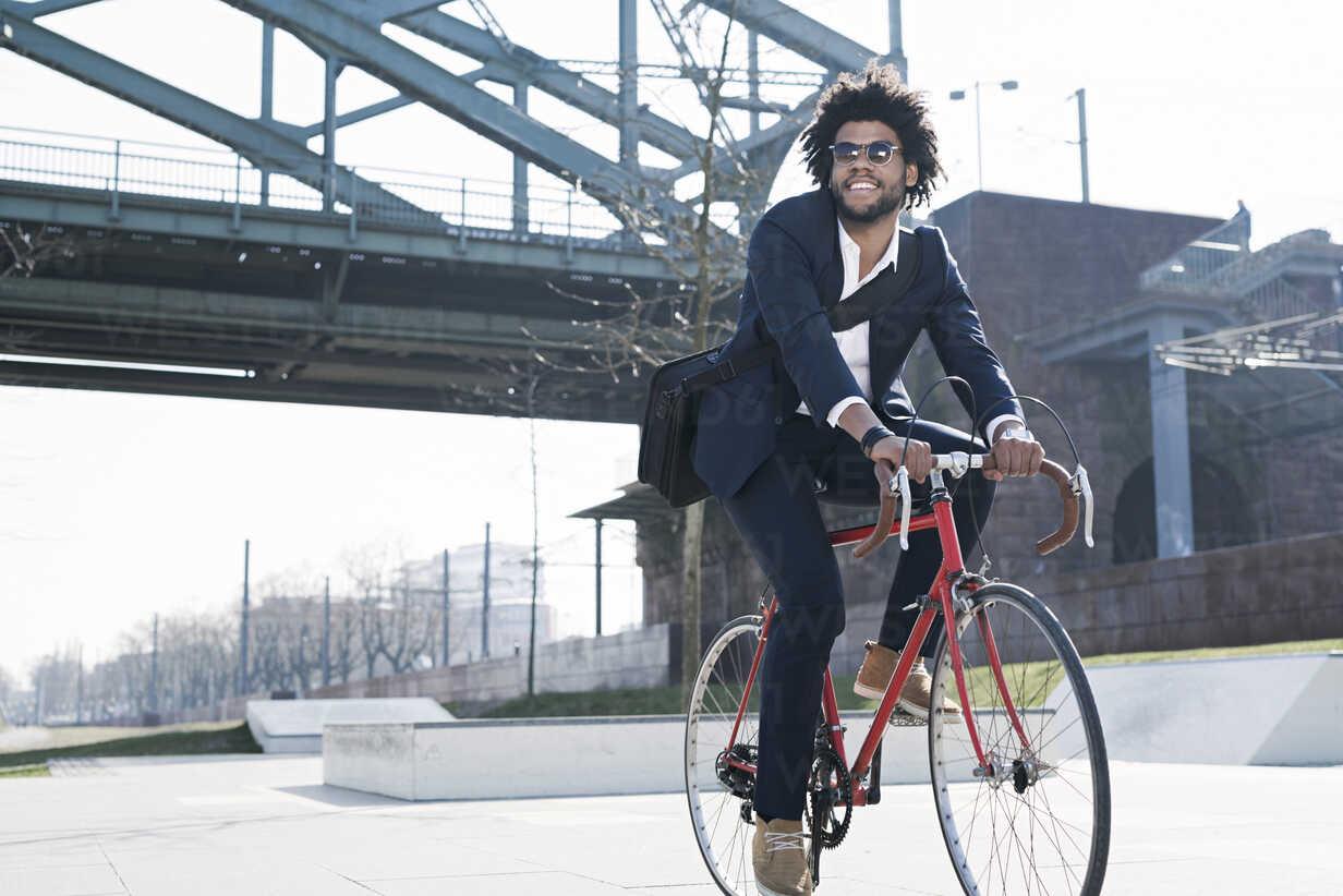 Smiling businessman riding bicycle at riverside bridge - SBOF00677 - Steve Brookland/Westend61
