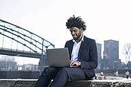 Smiling businessman sitting at the riverside using laptop - SBOF00680