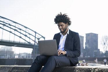 Smiling businessman sitting at the riverside using laptop - SBOF00680