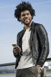 Smiling man with earphones listening to music on his smartphone - SBOF00686