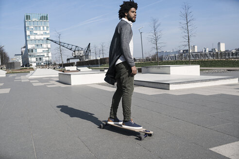 Young man riding longboard in skatepark - SBOF00692