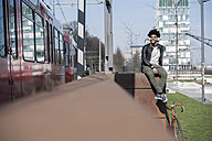 Smiling man sitting on wall listening to music next to passing train - SBOF00701