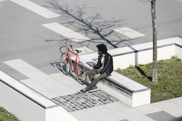 Man sitting in city skatepark holding his smartphone next to his bicycle - SBOF00704
