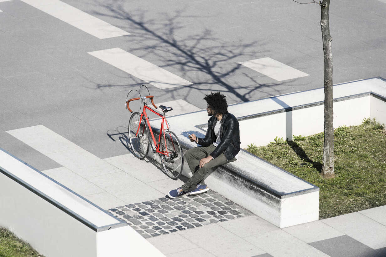 Man sitting in city skatepark holding his smartphone next to his bicycle - SBOF00704 - Steve Brookland/Westend61