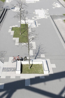 Man relaxing in city skatepark with smartphone next to his bicycle - SBOF00707