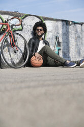 Smiling man sitting in front of grafitti wall next to his bicycle holding basketball - SBOF00716