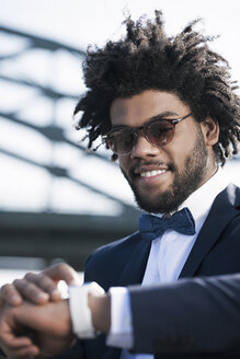 Smiling young man with sunglasses looking at his smartwatch - SBOF00719