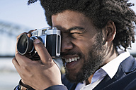 Close-up of smiling man taking a picture with a vintage camera - SBOF00725