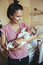 Happy mother holding her newborn baby in hospital - MFF03982