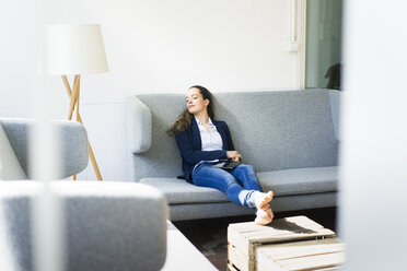 Businesswoman sitting on couch relaxing - JOSF01750