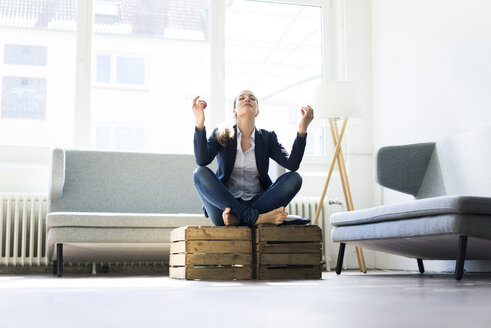 Businesswoman sitting on crate practising yoga - JOSF01753
