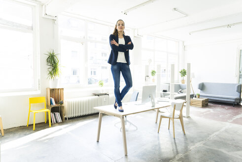 Portrait of businesswoman standing on table in a loft - JOSF01762
