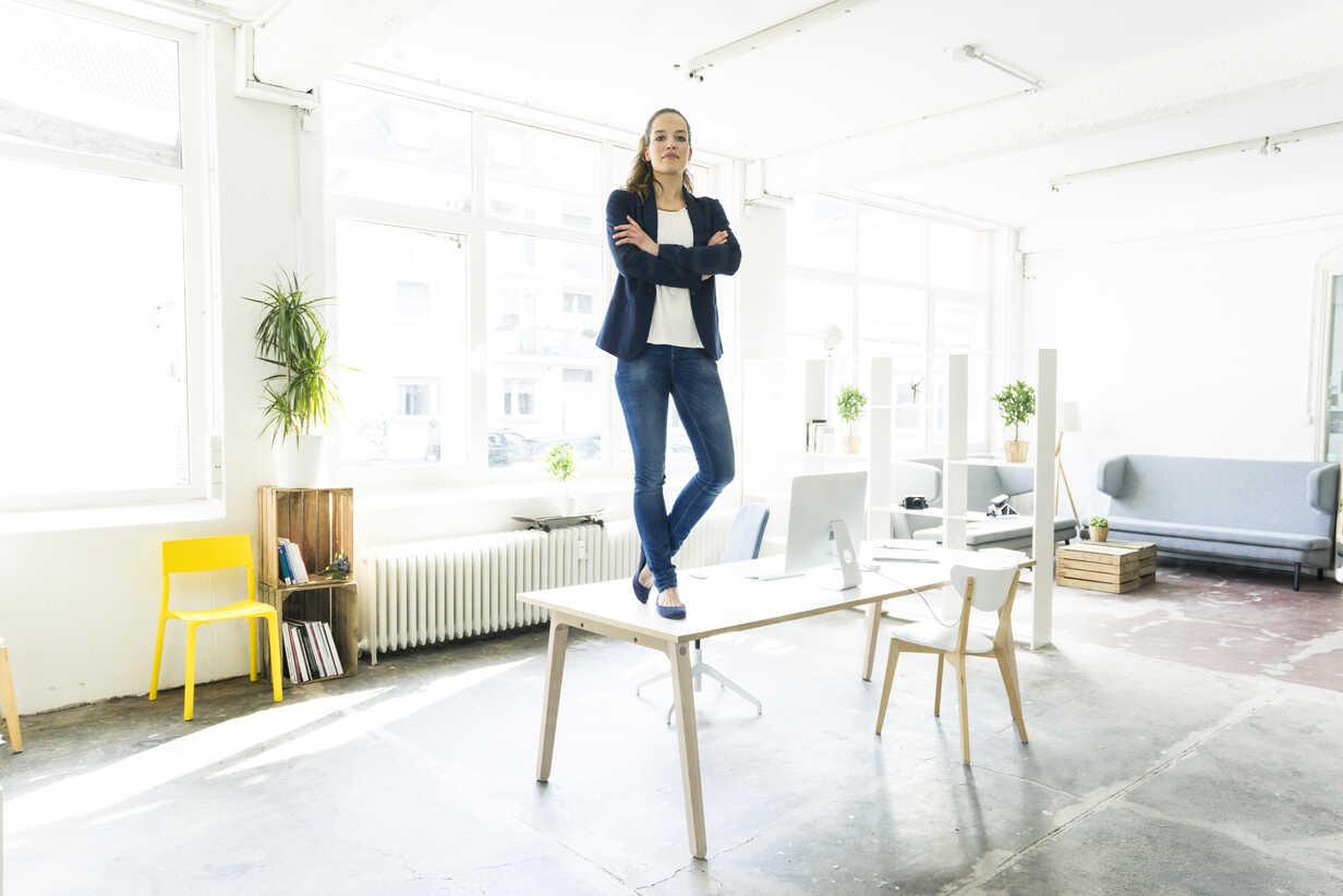 Portrait of businesswoman standing on table in a loft - JOSF01762 - Joseffson/Westend61