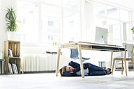 Businesswoman lying under the table in office sleeping - JOSF01774