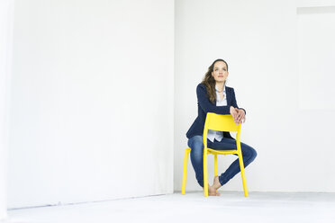 Businesswoman sitting on a yellow chair thinking - JOSF01783