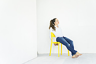 Woman sitting on a yellow chair - JOSF01786
