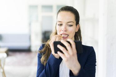 Businesswoman holding cell phone applying lipstick - JOSF01795