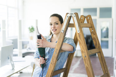 Portrait of woman at ladder holding electric drill - JOSF01798