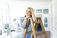 Portrait of smiling woman leaning on ladder - JOSF01801
