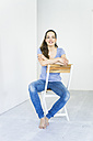 Portrait of woman sitting on a chair - JOSF01804