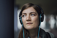 Portrait of daydreaming young woman listening music with headphones - JSCF00005