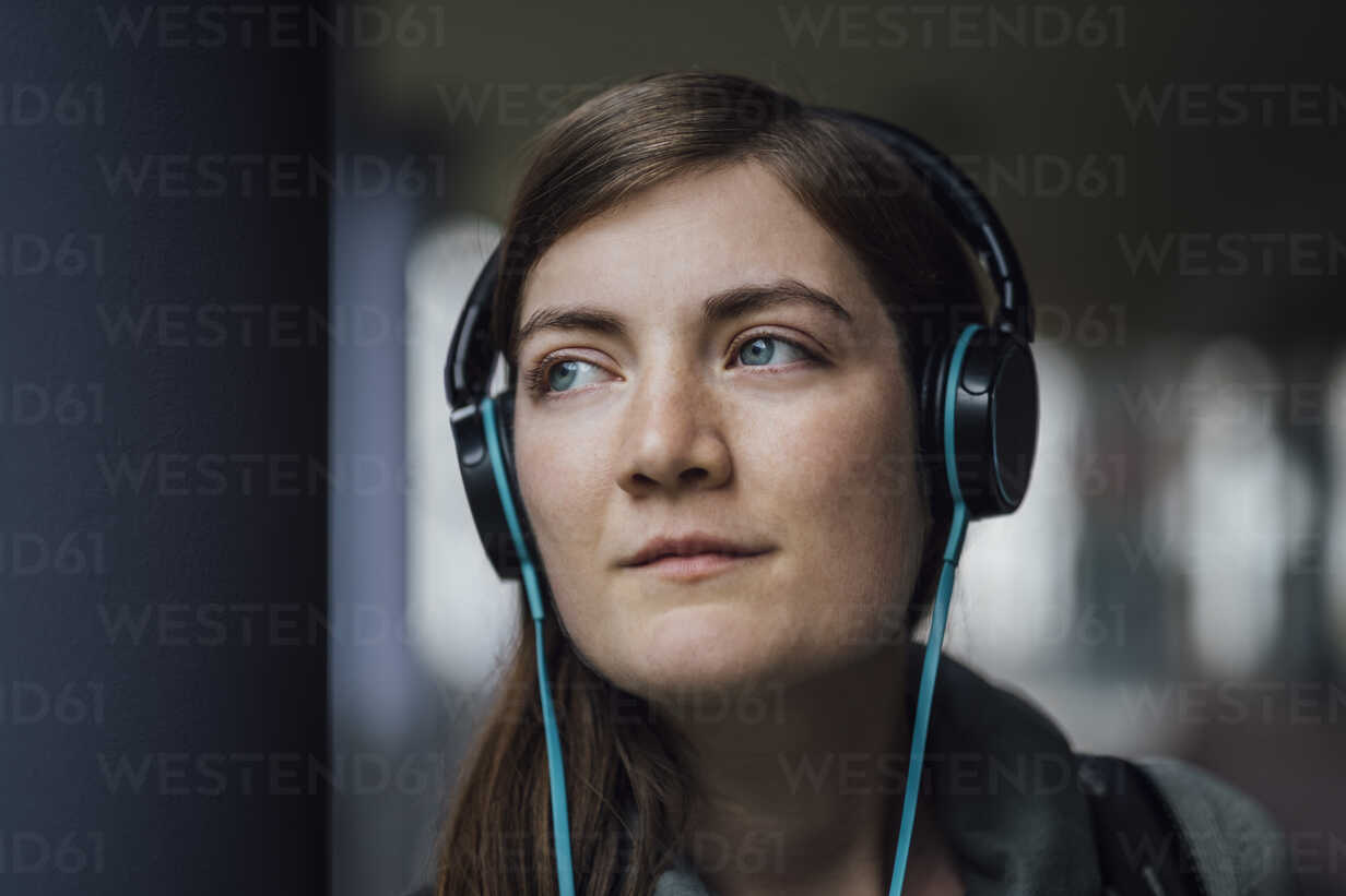 Portrait of daydreaming young woman listening music with headphones - JSCF00005 - Jonathan Schöps/Westend61