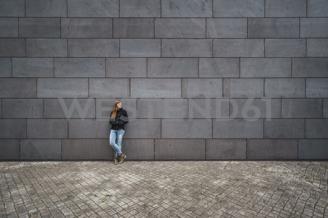 Young woman standing in front of grey facade waiting - JSCF00008