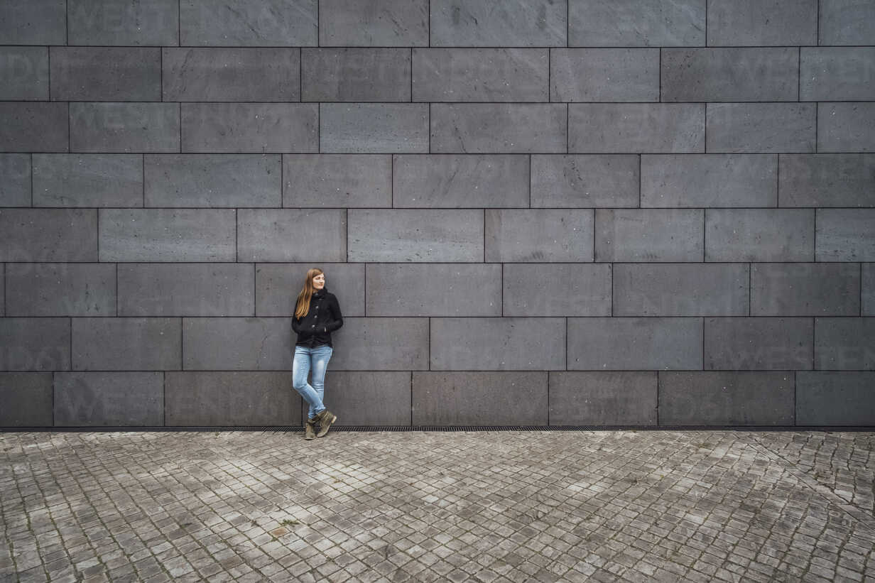 Young woman standing in front of grey facade waiting - JSCF00008 - Jonathan Schöps/Westend61