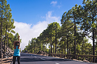 Spain, Tenerife, Woman training on empty road - SIPF01772