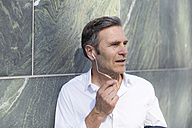 Mature businessman with earphones at a wall - FKF02522