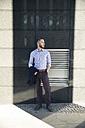 Businessman standing outdoors looking sideways - FKF02525