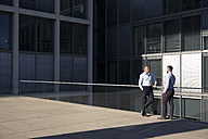 Two businessmen talking outside office building - FKF02534